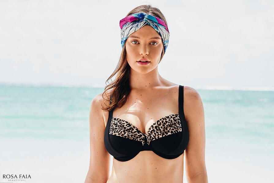 Junge Frau mit Turban im schwarzen Bikini mit Leo Print vonRosa Faia am Strand