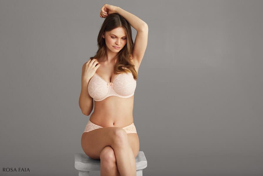 Junge Frau mit großer Oberweite sitzt in Unterwäsche von Rosa Faia auf einem Hocker